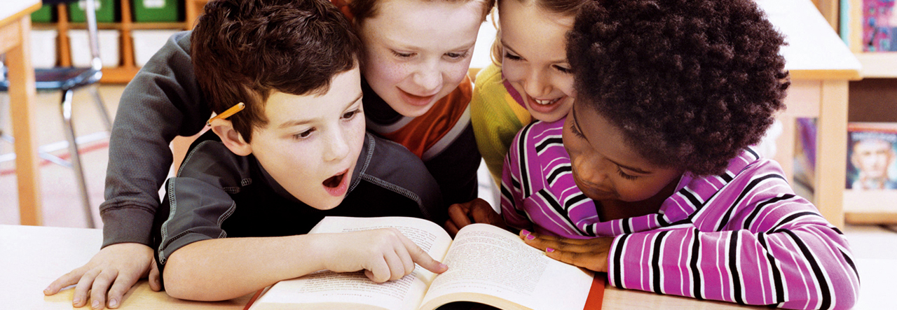 Group of children reading a book