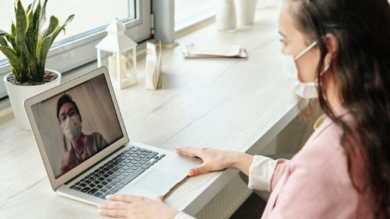 Woman is having video conference in front of a laptop PC