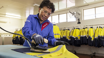 Woman ironing bright yellow uniform jackets in the background