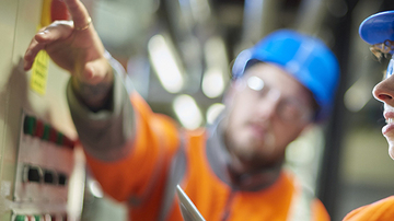 Two men in hard hats pointing towards the camera