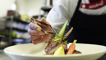 Chef adding a garnish to a dish of food